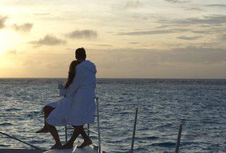 Katamaran segling par i solnedgång