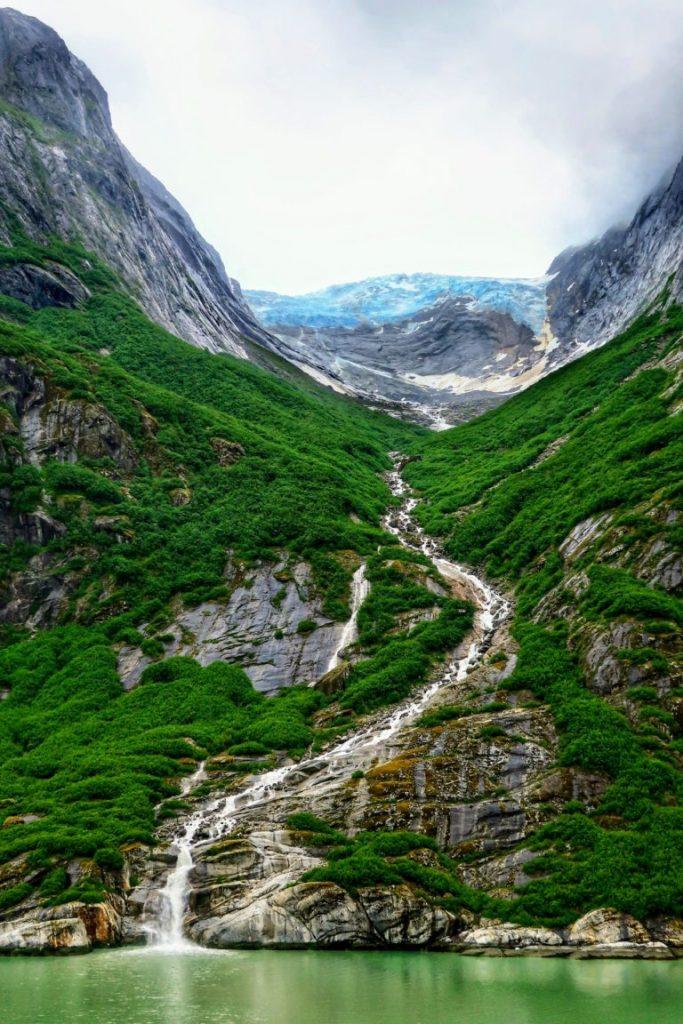 Vattenfall i Alaska längs gröna berg