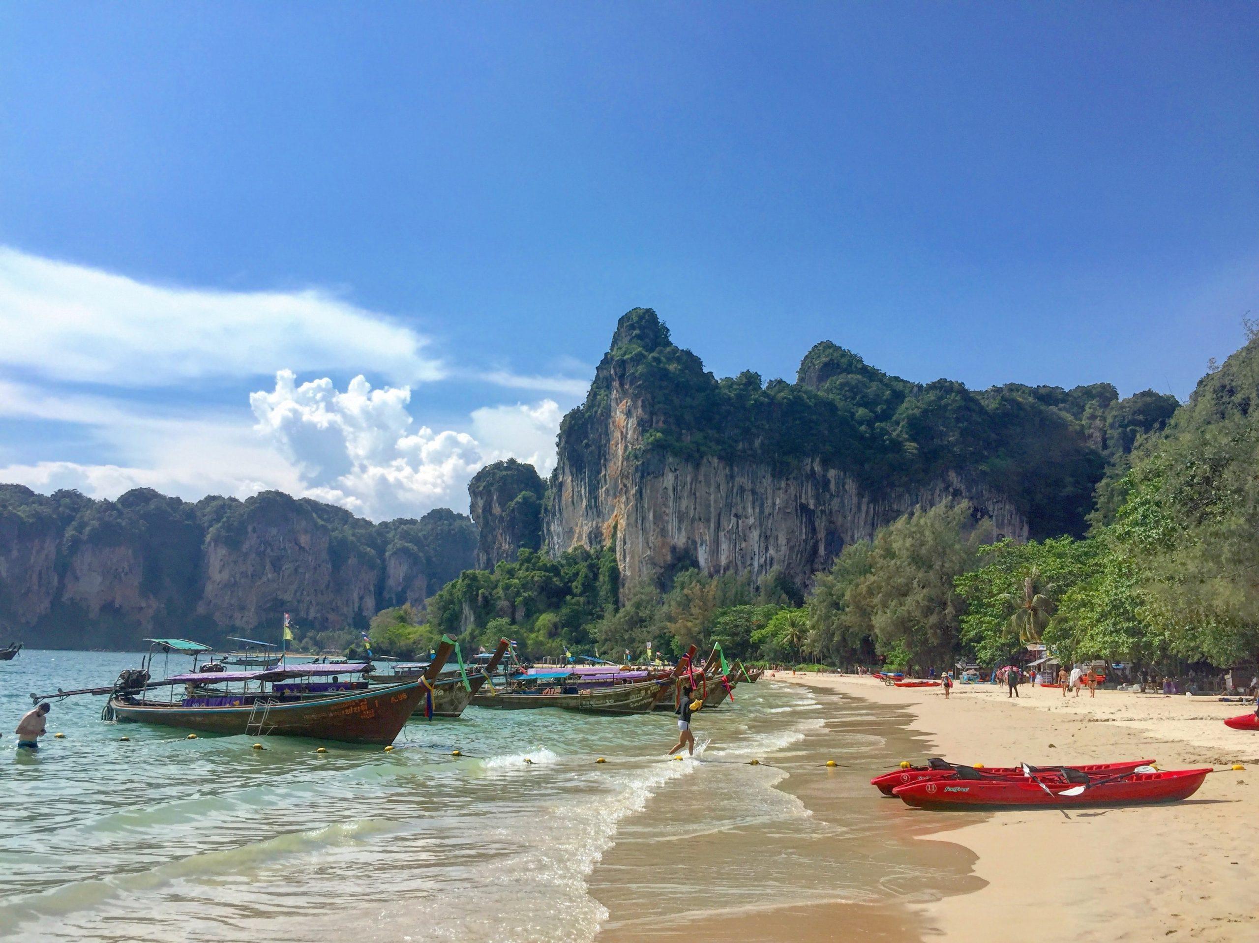 Sandstrand med båtar i Thailand