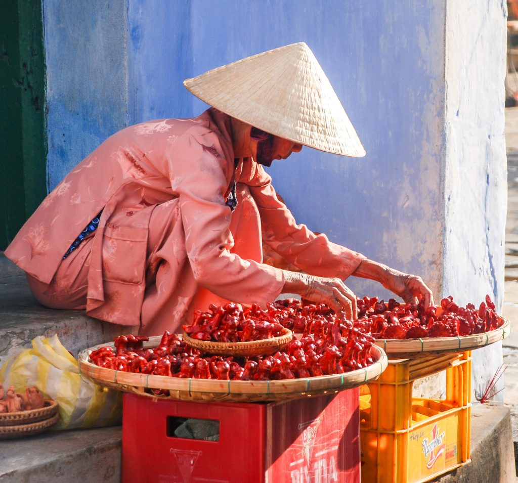 Vietnamese street vendor sell small ceramic statues