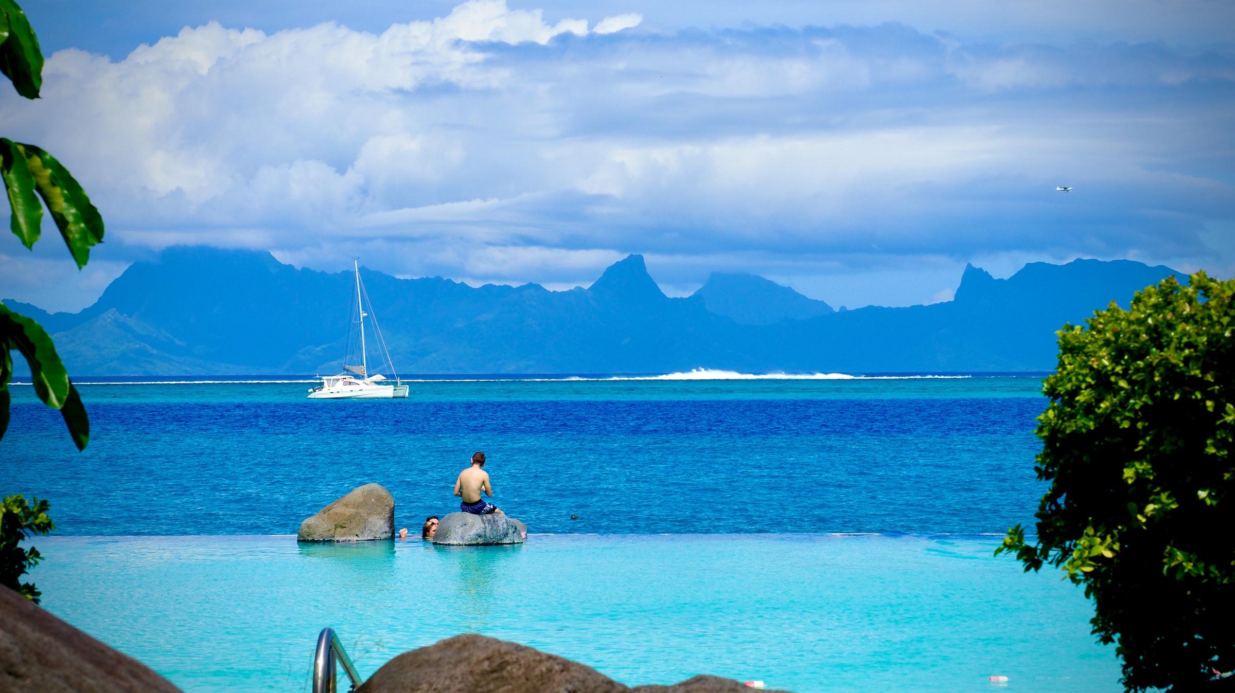 man som sitter på en sten i tahitis blå hav
