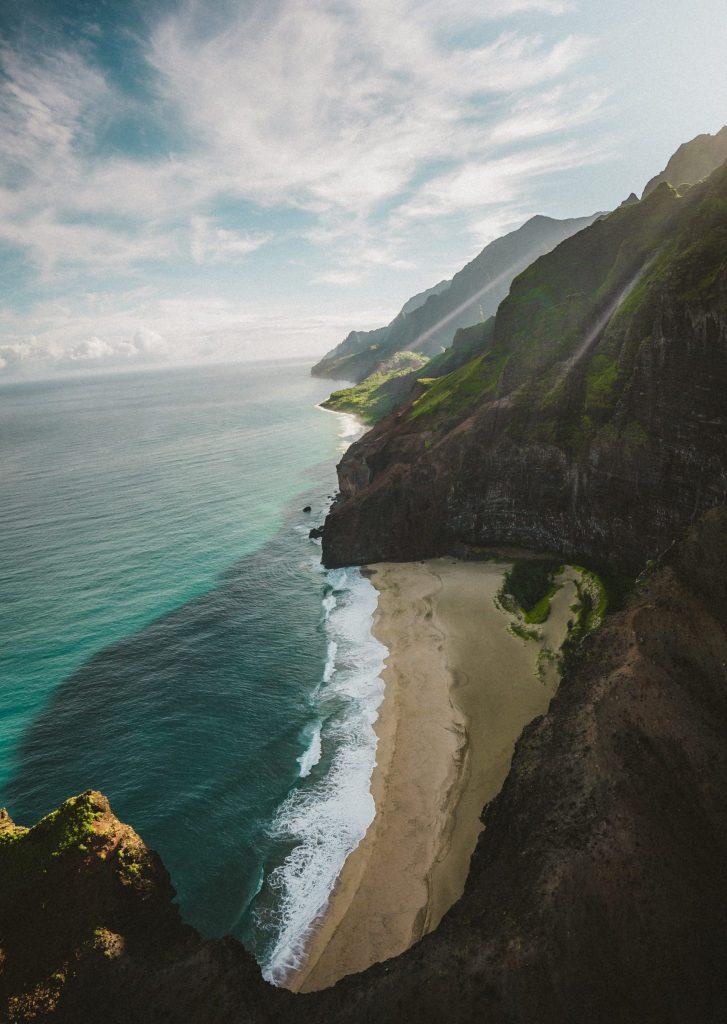 Kauaiöns kust med blått vatten och höga berg