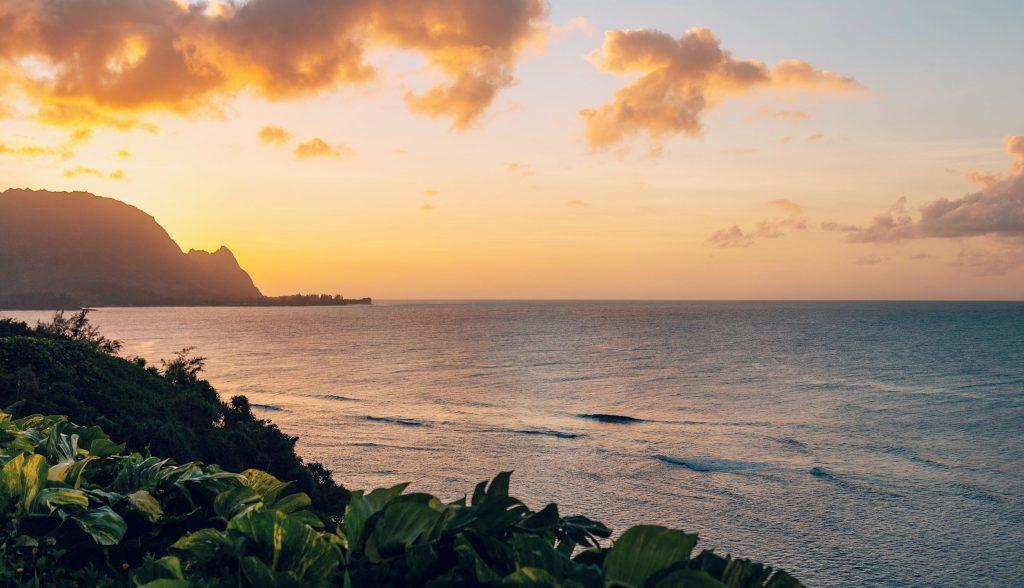 Solnegång på Kauai ön i Hawaii med rosa och gula färger över Stilla Havet