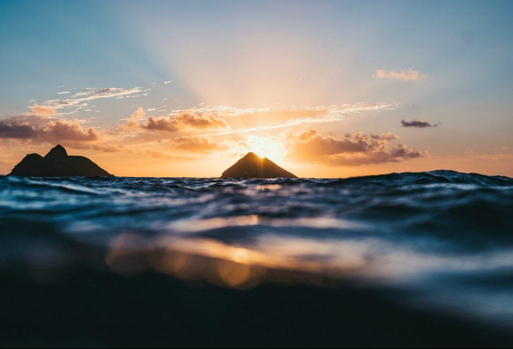 Oahu ön med solnedgång bakom bergen med havet i närbild