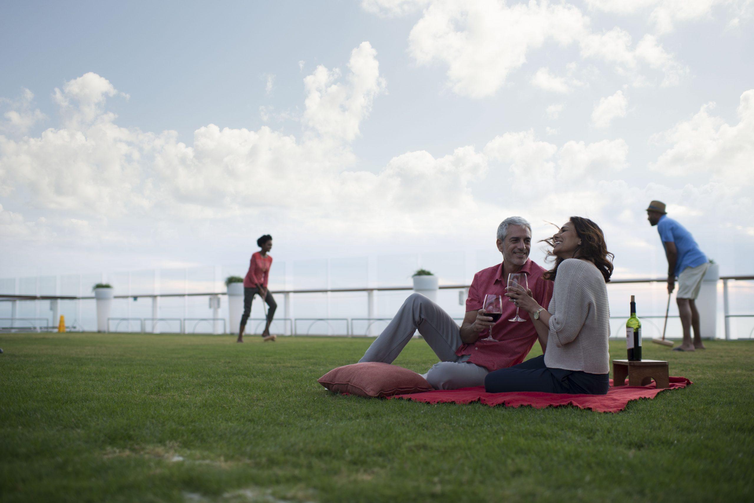 Picknick på grön gräsmatta omborrd Celebrity Equinox