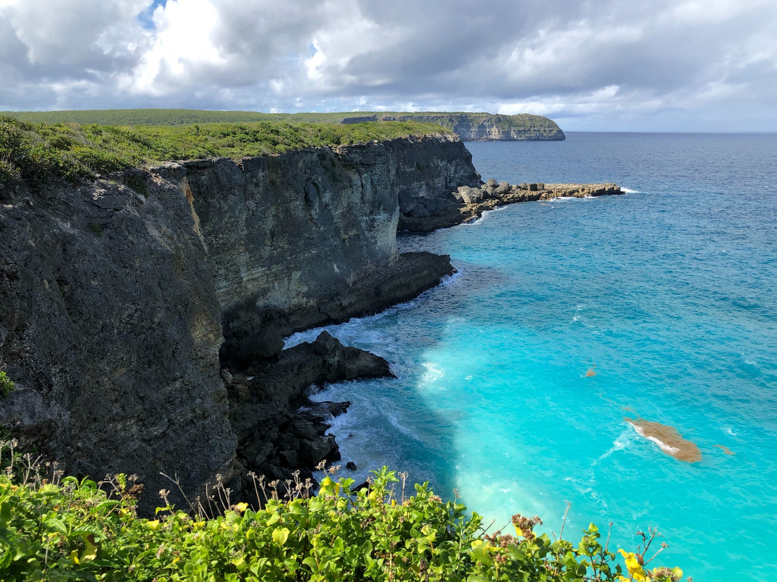 Branta klippor och klarblått vatten i Guadeloupe