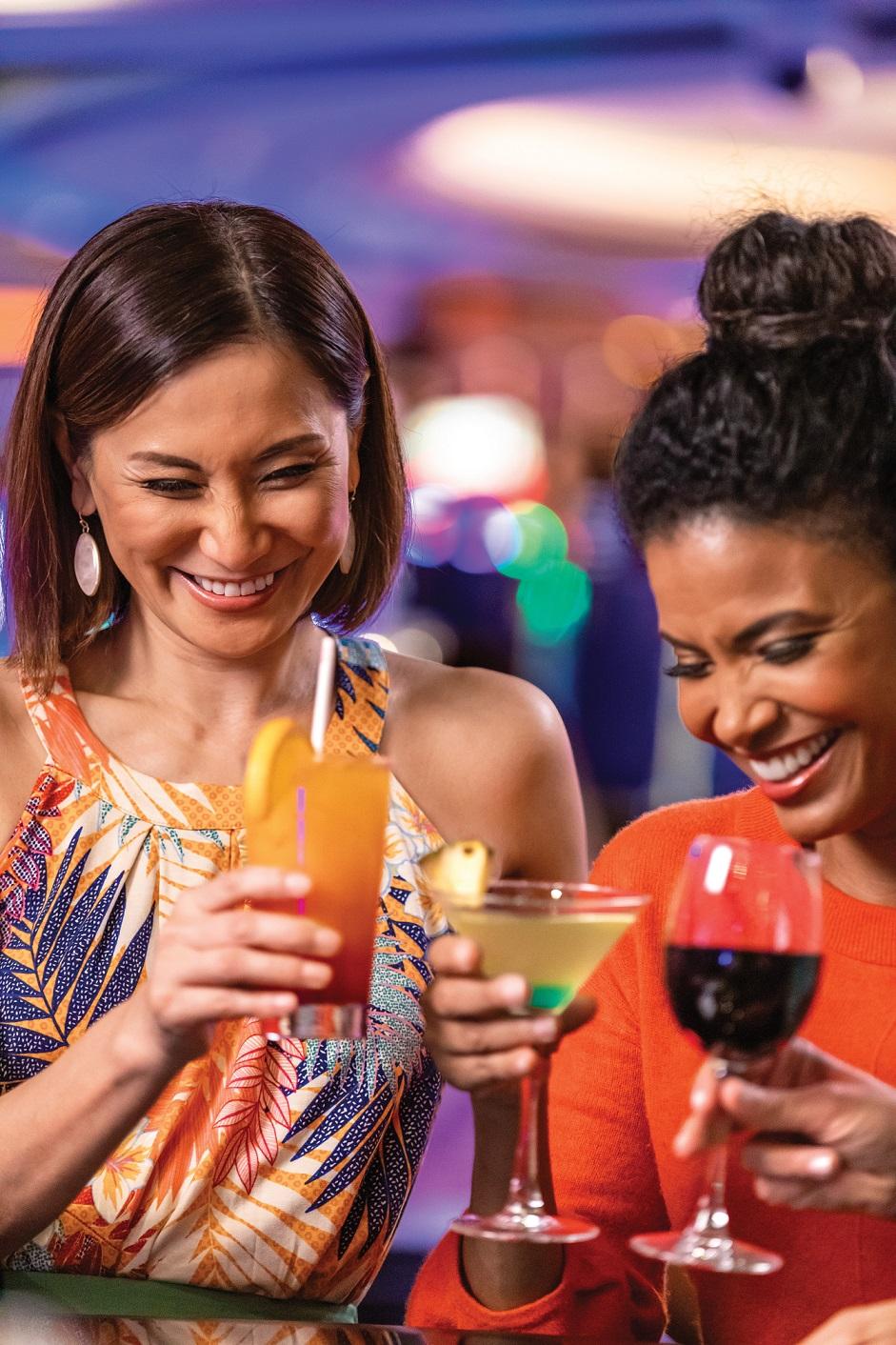 Två kvinnor njuter av drinkar i casinot ombord Navigator of the Seas