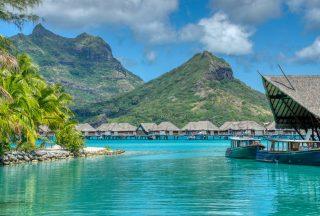 höga berg vid havet med hus på vattnet thaiti